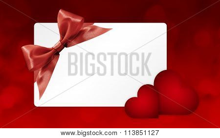 Gift Card With Red Ribbon Bow And Hearts Isolated On Red Background.