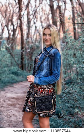 Young and beautiful  smiling ukrainian blonde girl walks in the park