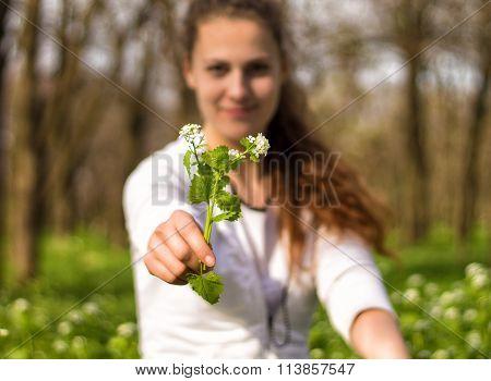 Young and happy ukrainian girl is giving flowers Capsella bursa-pastoris