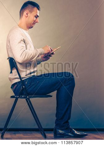 Man Using Mobile Phone Sitting In Chair.