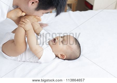 Chinese Father And Son Playing In Bed