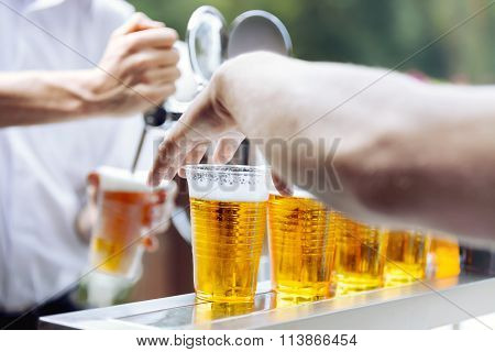 Man drawing beer. Hand takes beer plastic cup