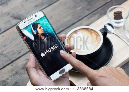 CHIANG MAI THAILAND - NOV 20 2015: A man hand holding screen shot of apple music app showing on samsung galaxy s6 edge. Apple Music is a beta version on android.