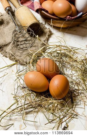 Eggs In A Cup With Hay And Tools - Whisk, Pestle.
