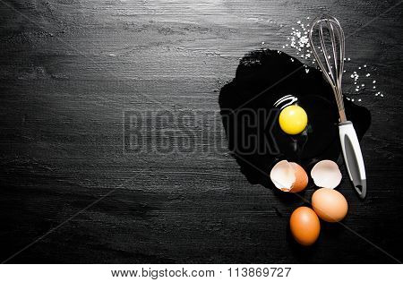 Broken Eggs With Whisk . On Black Wooden Background.