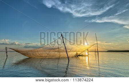 The fishermen mending their nets sailing on his lift net