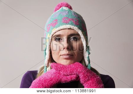 woman wearing a knitted cap holding her hands beneath her chin