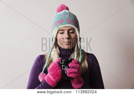 woman wearing a knitted cap holding a cup
