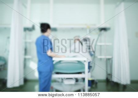 Medical Workers Taking Care Of Patient, Blurred Background.