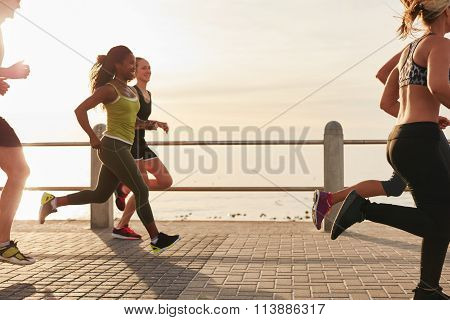 Woman Running With Friends On Seaside Promenade