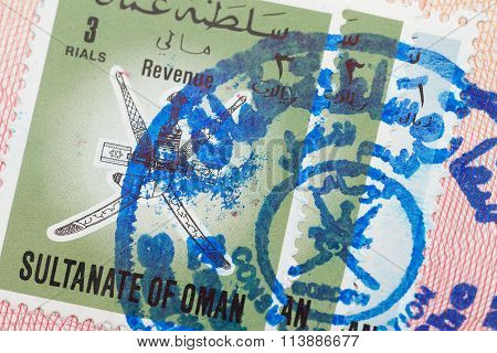 Passport page with the Sultanate of Oman visa and immigration control stamp.