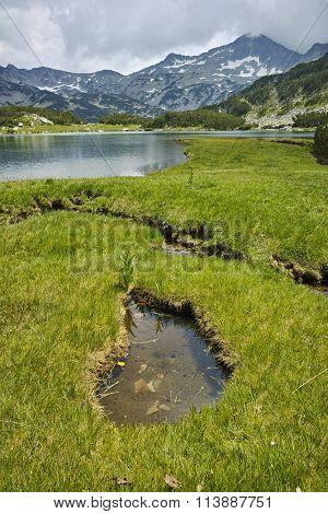 Landscape of Banderishki Chukar peak and reflection in Muratovo lake, Pirin Mountain