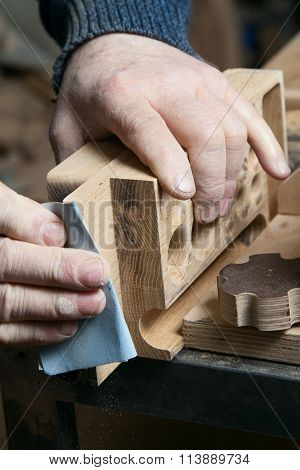 Man sandpaper grinds wood product in one studio