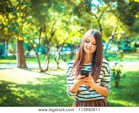 Happy beautiful young Caucasian girl with smart phone outdoors on sunny summer day tex-ting