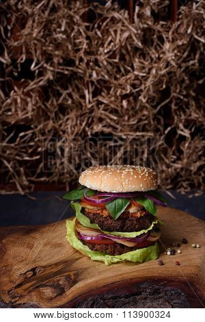 Vegetarian burger with falafel patty on rustic wooden board, hay straw texture background.