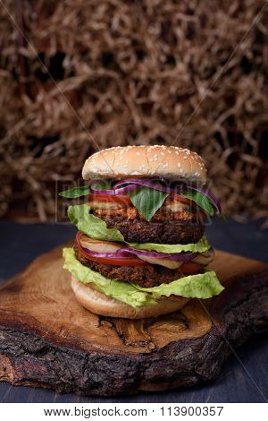 Burger with succulent beef patty and fresh vegetable ingredients served on a rough wood board.