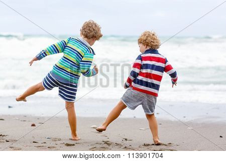 Two kid boys playing on beach on stormy day