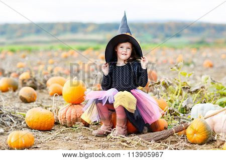 little girl wearing halloween witch costume on pumpkin patch
