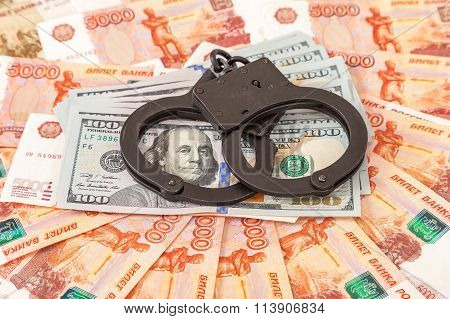 Steel Handcuffs Lying On A Stack Of Dollar Bills On The Background Of Russian Rubles