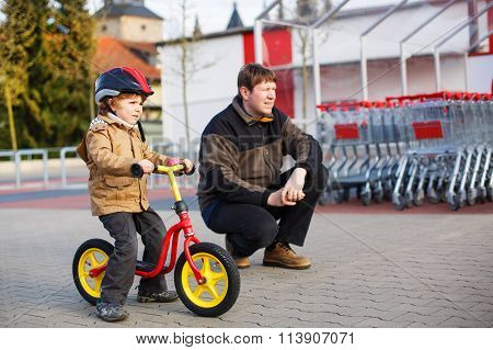 Little toddler boy with bicycle and his father in the city