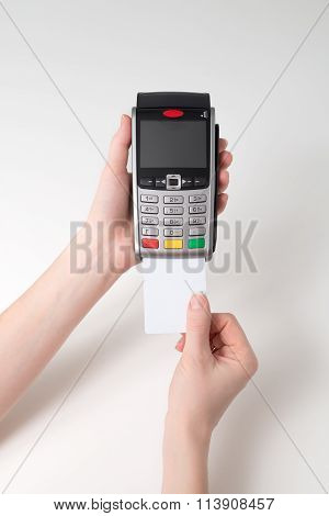Hand with credit card swipe through terminal
