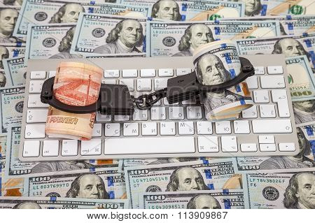 Steel Handcuffs, Rolls Of Russian Rubles And Dollars Lying On A Computer Keyboard On The Background