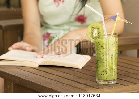 Glass of kiwi smoothie and a book reading
