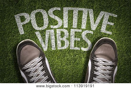 Top View of Sneakers on the grass with the text: Positive Vibes