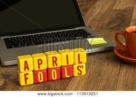 April Fools' written on a wooden cube in a office desk