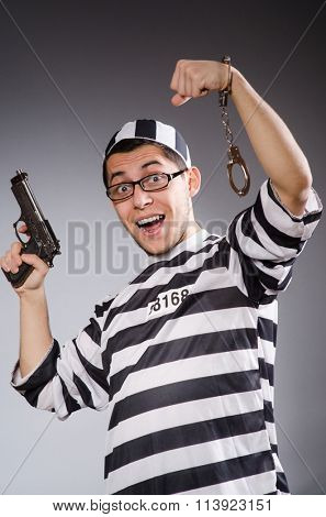Funny prisoner with weapon isolated on gray
