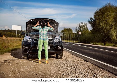 Woman on the road near the car. Damage to vehicle problems on the road.