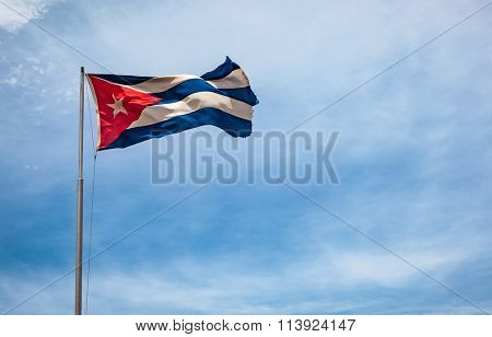 Cuban flag flying in the wind on a backdrop of blue sky. National symbol.