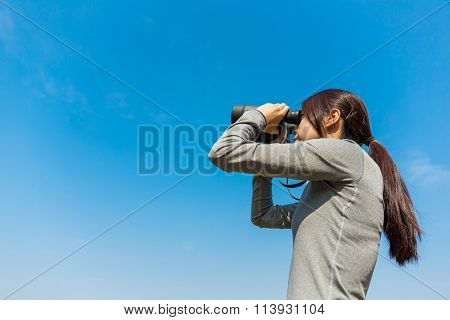 The side profile of woman looking though binoculars