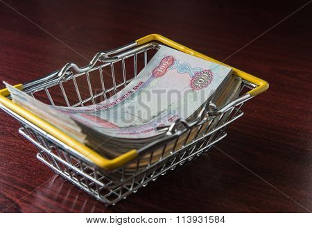 Hundred dirham notes placed in a shopping cart - An idea.