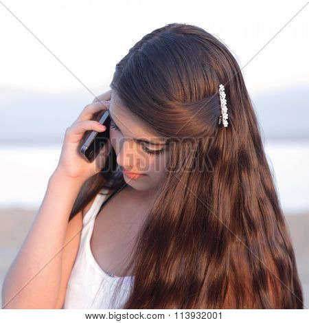 Young causcasian beautiful teenage girl with long dark hair talking on a cell phone.