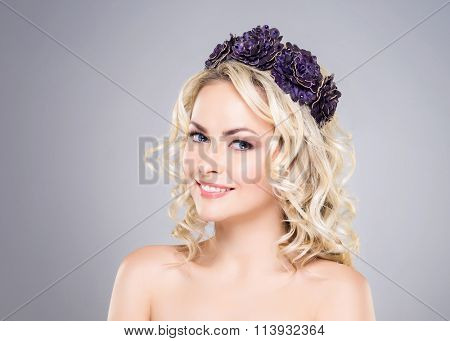Beautiful, smiling, young lady wearing bijouterie over grey background.