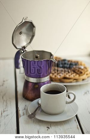 Cup of coffee, coffee pot and waffles with fresh honeysuckle