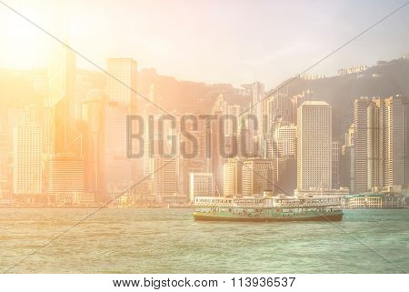 Famous ferry on Victoria harbor in Hong Kong with tall buildings.