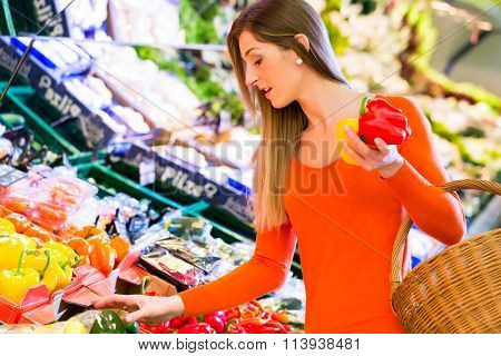 Woman selecting paprika while grocery shopping in supermarket