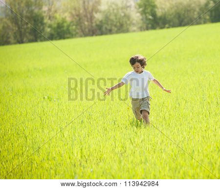 Child having happy time in nature on meadow