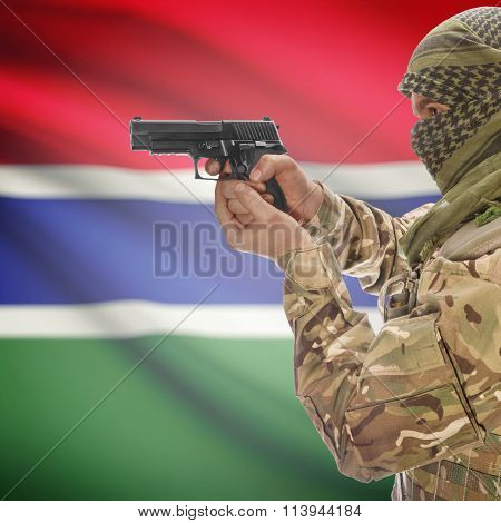 Male In With Gun In Hand And National Flag On Background - Gambia