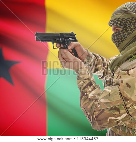Male In With Gun In Hand And National Flag On Background - Guinea-bissau