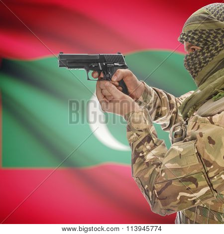 Male In With Gun In Hand And National Flag On Background - Maldives