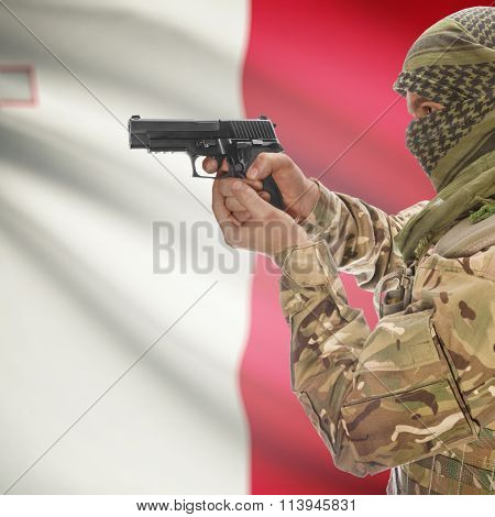 Male In With Gun In Hand And National Flag On Background - Malta