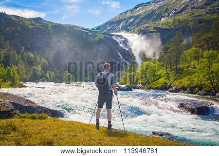 Men With A Backpack Watching The Waterfall, Norway