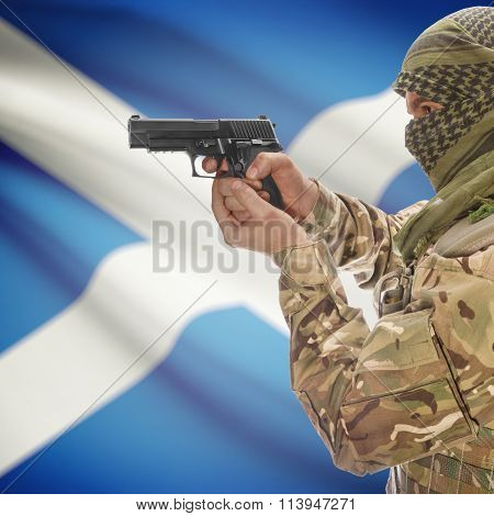 Male With Gun In Hand And National Flag On Background - Scotland