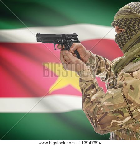 Male In With Gun In Hand And National Flag On Background - Suriname