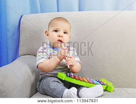 Adorable baby with plastic colourful xylophone on sofa in the room