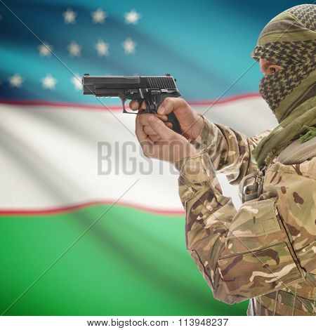 Male With Gun In Hand And National Flag On Background - Uzbekistan