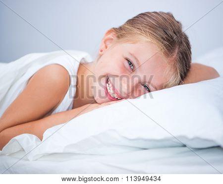 little cute girl woke up in white bed